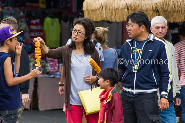 Tourists trying Korean Tornado Potatoes at the market